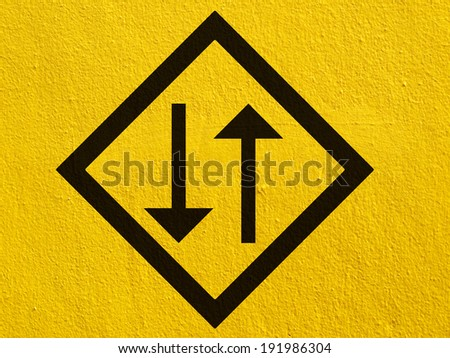 a black two way arrow points painted on a stucco wall outside - stock photo