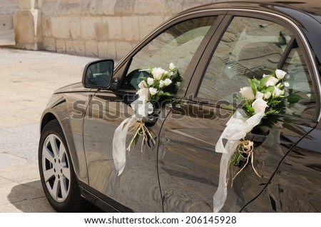 A black wedding car decorated with white roses - stock photo