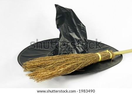 A black witch hat and broomstick isolated on a white background - stock photo
