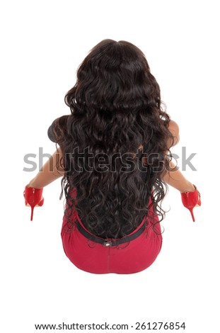 A black woman with long black curly hair and red skirt sitting from the