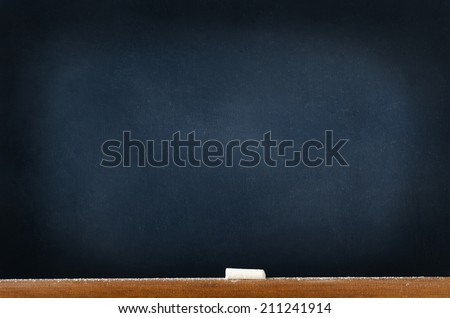 A blackboard (chalkboard) left blank to provide copy space; with a wooden ledge at the bottom, holding a piece of used chalk and sprinklings of fallen chalk dust. - stock photo