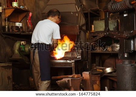 A Blacksmith heating metal in front of a forge.