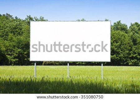 A blank advertising billboard immersed in a wheat field - stock photo