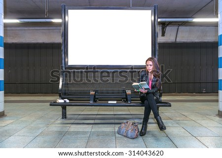A blank billboard at an underground railway station with a woman sitting on a bench underneath, reading a book - stock photo