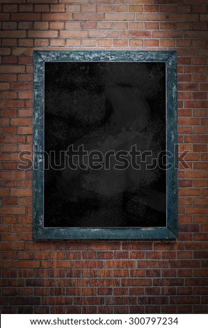 A blank blackboard under a spotlight and hanging on a brick wall. - stock photo