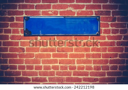 A Blank Blue Sign For Your Text On A Red Brick Wall - stock photo