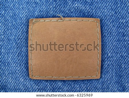 A blank, brown leather tag sewn onto blue denim.