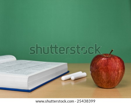 A blank chalkboard with an apple, a book and some chalks. - stock photo