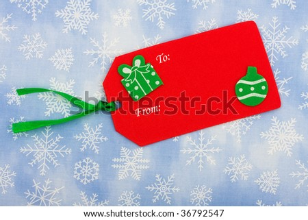 A blank Christmas gift tag sitting on a snowflake background, Christmas present