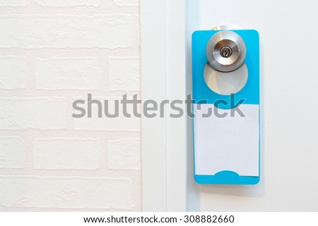 A blank door hanger on a door, with copy space, add text or graphic - stock photo