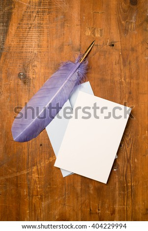 A blank greeting or invitation card with envelope and purple quill on a wooden surface for copy space. - stock photo