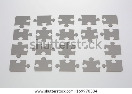 A blank jigsaw puzzle with one piece missing. - stock photo