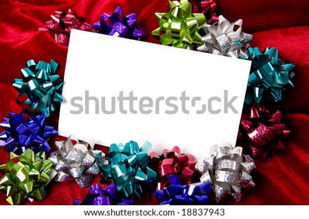 A blank note-card surrounded by Christmas decoration bows on a red background, add copy or graphic