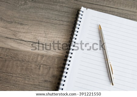 A blank notebook with a pen - stock photo