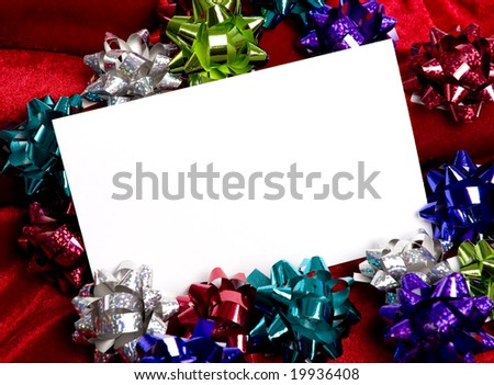 A blank notecard surronded by Christmas decoration bows on a red background, add copy or graphic, Christmas party invitation,