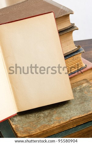 A blank page offers copy space against a background of stacked antique books - stock photo