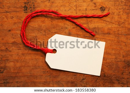 A blank paper tag with red string, on a old wooden desk  - stock photo