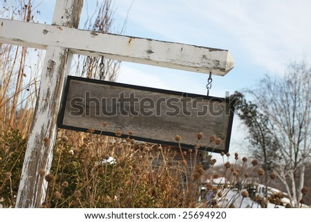 A blank, rustic wooden sign with signs of wear. - stock photo