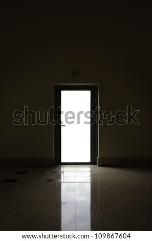 A blank space for text  on the glass pane of a metal door frame silhouette with reflection on the floor. - stock photo