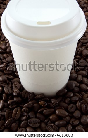 A blank throw-away coffee cup on a coffee bean background.