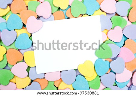 A blank Valentine's card in a pile of heart shaped pastel candies. Blank card is for placement of copy. - stock photo