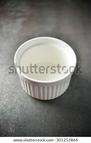 A blank white bowl on dark background, closeup.
