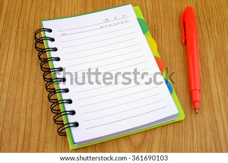 A blank white notebook with pen on a wooden background.