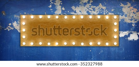 A blank wooden signboard illuminated by rows light-bulbs, on a blue weathered concrete wall.