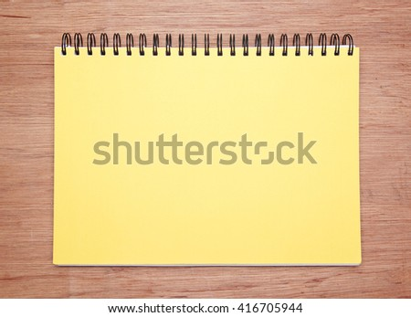 a blank yellow notebook on a wooden table. above view.