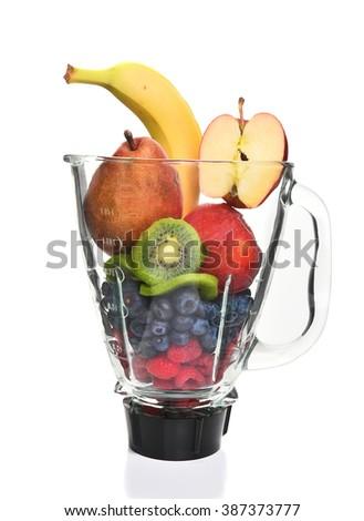 A blender filled with fresh whole fruits for making a smoothie or juice. Healthy eating concept.