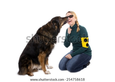 A blind woman is touching her guide dog and cuddles with him - stock photo