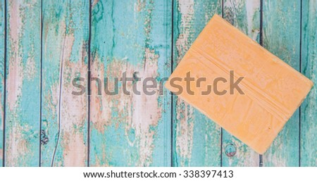 A block of cheddar cheese over wooden background