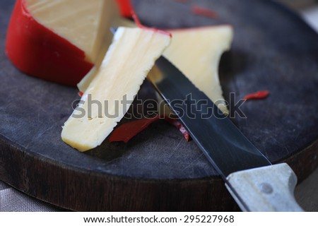 A block of cheese on a cutting board, slices cut - stock photo