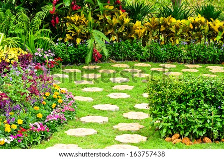 A block of stone walkway its way through a tranquil garden.