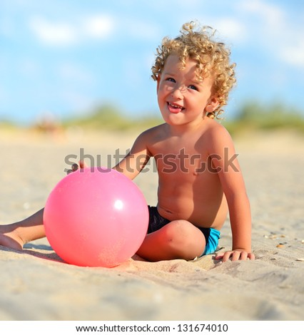 a blond boy plays a red ball
