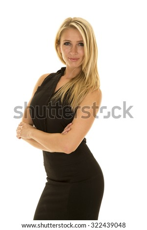 A blond business woman in her black dress with arms folded and a smile on her lips.