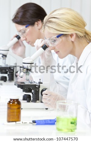 A blond female medical or scientific researcher or doctor using her microscope in a laboratory with her  colleague out of focus behind her. - stock photo