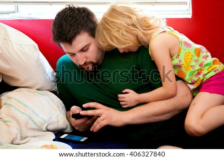 A blond girl cuddles on top of her dad as he checks his phone.  Another phone lays next to him. - stock photo