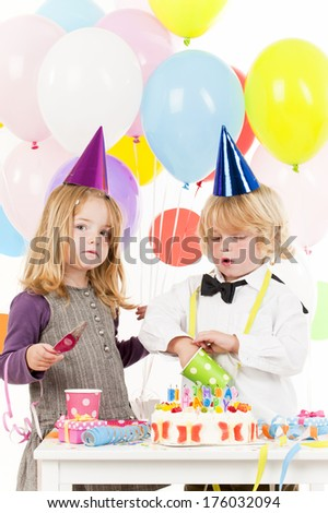 A blond haired boy and girl at their birthday party having fun.