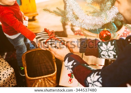 A blond haired toddler and her family exchanging Christmas gifts near the Christmas tree on Christmas Day to celebrate the event. The child takes with the hand the gift his father gives him  - stock photo
