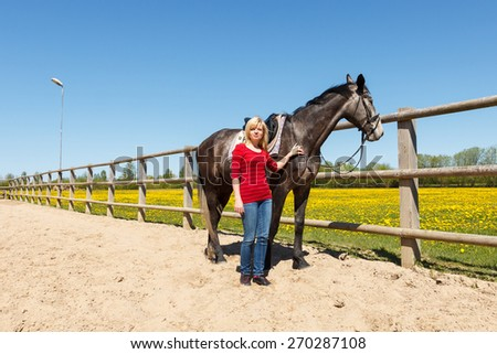 A blond haired woman by a dark horse in a fenced area - stock photo