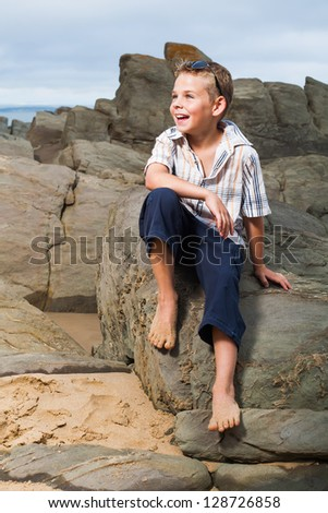 A blond little boy are being photographed on the beach. - stock photo