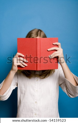 a blond shy girl hiding her face behind a book - stock photo