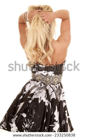 A blond woman in a black and white dress from the back. - stock photo