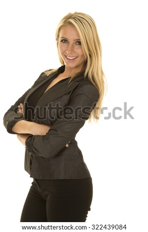 A blond woman in her business clothing with her arms folded and a smile on her face