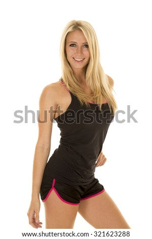 a blond woman in her fitness clothing with a smile on her face, posing. - stock photo