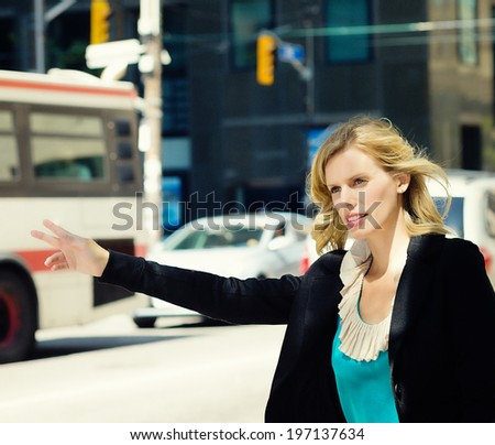 A blond woman is standing on a street holding her arm out. - stock photo