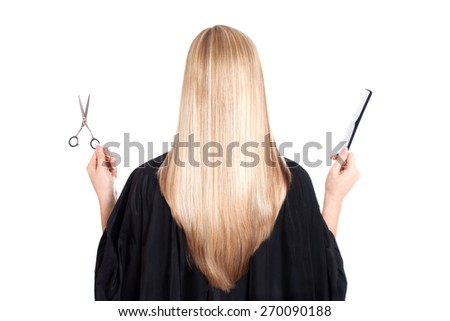 A blond woman on white background holding scissors in her left hand and a black comb in her right. She has beautiful, long and healthy hair.  - stock photo