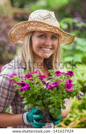 A blond woman with a hat is holding flowers in the garden with gloves