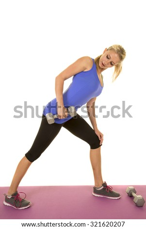 a blond woman working out with weights on a fitness mat.